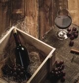 Bottle, glass and red grape on a wooden table  — Stock Photo