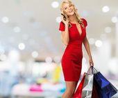 Mulher loira sorridente feliz com sacos de compras e telefone móvel no interior da loja — Fotografia Stock