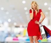 Happy smiling blond woman with shopping bags and mobile phone in shop interior  — Стоковое фото