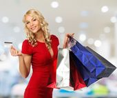 Smiling young blond woman with shopping bags and payment card in shop interior — ストック写真