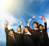 Happy multi ethnic group of graduated young students with scrolls against blue sky — Stock Photo