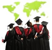 Group of graduated young students in black mantles against world map — Stock Photo