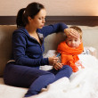 Young mother and her sick son in a bed — Stock Photo #46582853