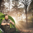Handsome traveler near tent with coffee cup in autumnal forest — Stock Photo #46582901