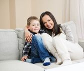 Happy young mother with her son on a sofa in home interior — Stock Photo