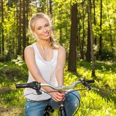 Smiling teenage girl with bicycle in a park on sunny day — Stock Photo