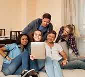 Group of young multi ethnic friends taking selfie in home interior — Stock Photo