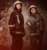 Two firefighters with helmet and axe in a smoke — Stock Photo