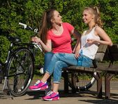 Two happy teenage girls with bicycles in a park  — Photo
