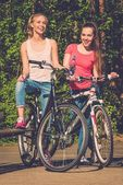 Two happy teenage girls with bicycles in a park  — Stock Photo