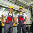 Two workers wearing safety hat in a factory control room — Stock Photo