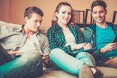 Three young students preparing for exams in apartment interior  — Foto de Stock