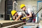 Worker and foreman in a safety hats performing quality check on a factory   — Stock Photo