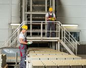 Worker and foreman in a safety hats on a factory   — Stock Photo