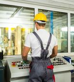 Operator wearing safety hat in a factory control room — Stock Photo