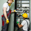 Two electricians in a safety hat and headphones on a factory — Stock Photo #47000003