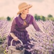 Woman in purple dress and hat with basket in lavender field — Stock Photo #47000253