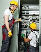 Two electricians in a safety hat and headphones on a factory — Stock Photo