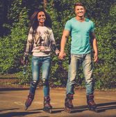 Multi ethnic teenage couple on a rollerblades in a park  — Stok fotoğraf