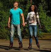 Multi ethnic teenage couple on a rollerblades in a park  — Foto de Stock