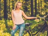 Beautiful teenage girl listens music on bicycle outdoors — Foto de Stock
