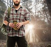 Handsome traveler with backpack and flask in autumnal forest  — Stock Photo