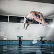 Young muscular swimmer jumping from starting block in a swimming pool — Φωτογραφία Αρχείου