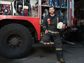 Cheerful firefighter near truck with equipment  — Stock Photo