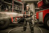 Firefighter holding water hose near truck with equipment  — Stock Photo