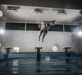 Young muscular swimmer jumping from starting block in a swimming pool — Stock Photo