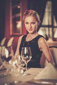 Krásná mladá dívka sama v luxusní restauraci — Stock fotografie