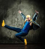 Man dancer in cap and jacket showing break-dancing moves — Stock Photo