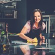 Young cheerful woman cleaning modern kitchen — Stock Photo #47742469