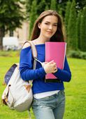 Beautiful young student girl in a city park on summer day — Stock Photo