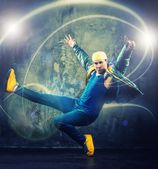 Stylish man dancer showing break-dancing moves with magic beams around him  — Stock Photo