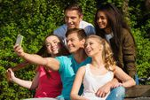 Multi ethnic group of sporty teenage friends in a park taking selfie — Stock Photo