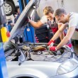 Two mechanics fixing car in a workshop — Stock Photo #48166123