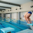 Young muscular swimmer in low position on starting block in a swimming pool — Stock Photo #48166405