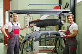 Two workers with car bodykit ready for painting in a workshop — Stock Photo
