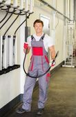 Cheerful serviceman holding hose with unbottled motor oil in a car workshop — Stock Photo