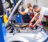 Two mechanics fixing car in a workshop — Stok fotoğraf