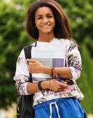 African-american student girl in a city park on summer day — Stock fotografie