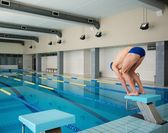 Young muscular swimmer in low position on starting block in a swimming pool — Stock Photo