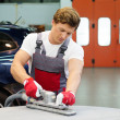 Young serviceman performing grinding with machine on a car bonnet in a workshop — Stock Photo #48591439