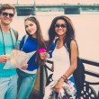 Multi-ethnic friends tourists with map and coffee cups near river in a city — Stock Photo #48591453