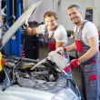 Two mechanics adding oil level in a car workshop — Stock Photo #48591595