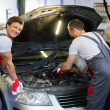 Two mechanics fixing car in a workshop — Stock Photo #48591599