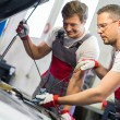 Two mechanics checking oil level in a car workshop — Stock Photo #48591605