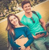Students couple preparing for final exams in a city park  — Stock Photo