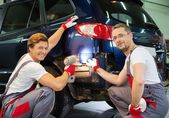 Two workers with colour samples choosing correct shade in a car body workshop  — Stockfoto